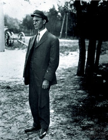 Wilbur Wright wearing his famous cap, standing, facing to his right at Le Mans, France