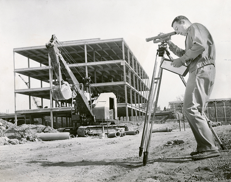 "Original DDN caption (Oct. 13, 1963): ""Dayton Campus: Airway Rd. Robert Eisenlohr Jr eng. surveys while building goes up in background."""