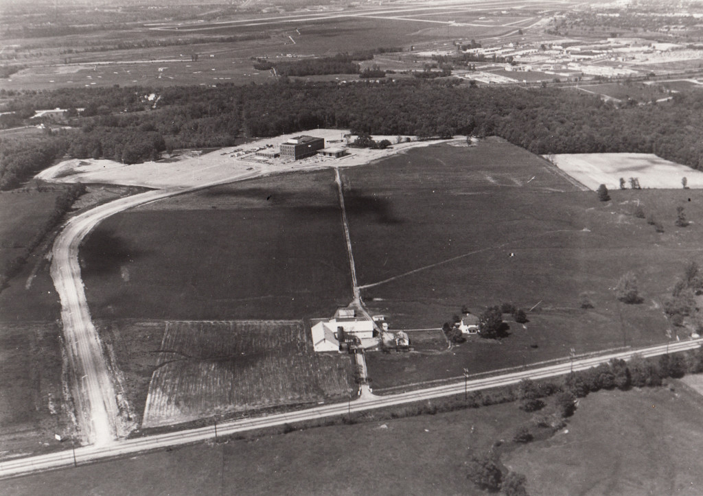 "Aerial view of Dayton Campus (now WSU), showing Airway Road and the Warner farm (foreground), the ""Dayton Campus"" sign (lower left), Allyn Hall (top center), and a portion of Wright-Patterson AFB (upper right). (University Archives)"