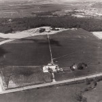 """Aerial view of Dayton Campus (now WSU), showing Airway Road and the Warner farm (foreground), the """"Dayton Campus"""" sign (lower left), Allyn Hall (top center), and a portion of Wright-Patterson AFB (upper right). (University Archives)"""