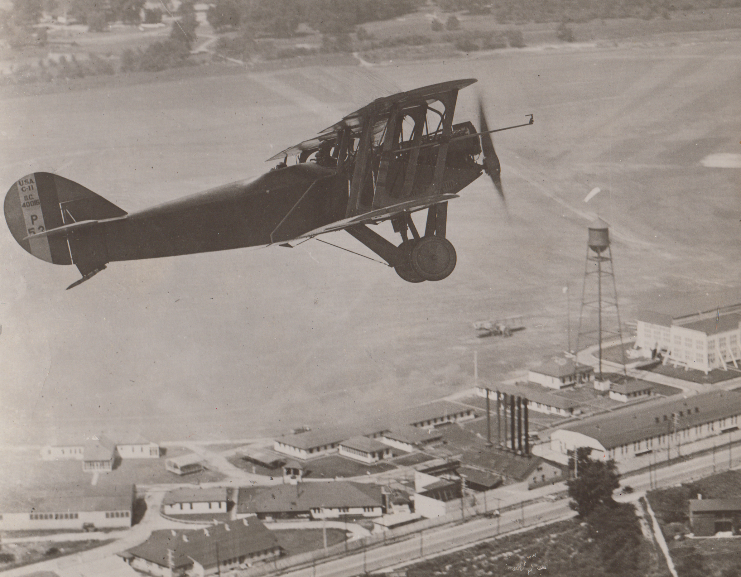 Airplane flying over McCook Field, undated