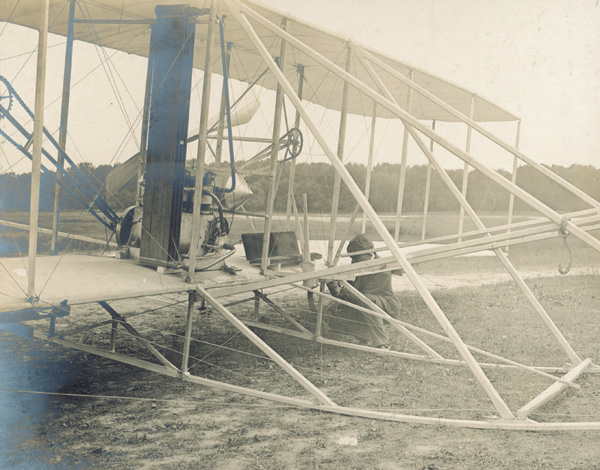 "Mechanic Charles E. ""Charlie"" Taylor making adjustments to the controls of the Wright Model A Flyer, 1908. (photo ms1_39_45)"