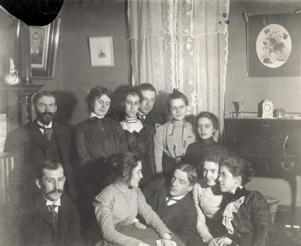 Party in the parlor of the Wright home at 7 Hawthorne Street, 1906. Top row, left to right: Dr. C. C. McClean, Mary Emmons, unidentified, unidentified, Mrs. McClean, and unidentified.. Bottom row: Orville Wright, unidentified, Nelson Emmons, Agnes Osborne, and Katharine Wright. (photo ms1_29_3_2)