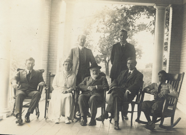 Group sitting and standing on the porch of the Wright Hawthorn Hill home, 1915. Left to right: Pliny Williamson, Katharine, Orville (standing), and Bishop Milton Wright, Earl N. Findley (standing), John R. McMahon, and Horace Wright. (photo ms1_26_5_5)
