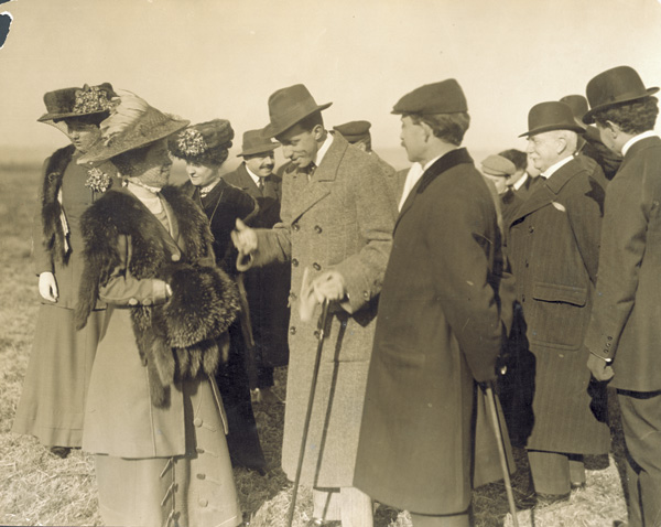 Katharine Wright speaks to Alfonso XIII, King of Spain, as Orville Wright, Mrs. Hart O. Berg, and others stand nearby, 1909. (photo ms1_18_1_17)