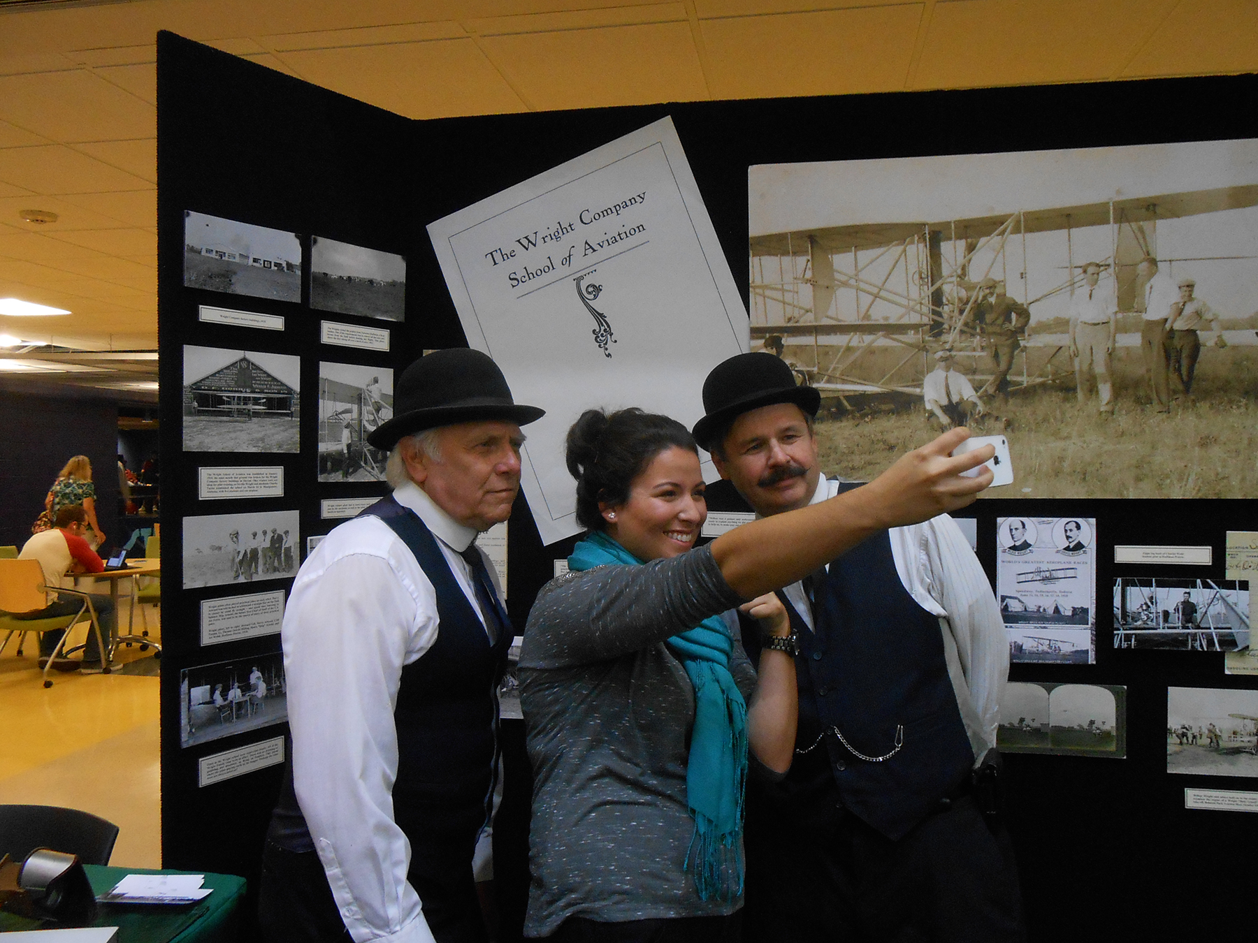 Public History grad student Susie Lang taking a selfie with Wilbur and Orville Wright at the 2014 Wright Brothers Day.