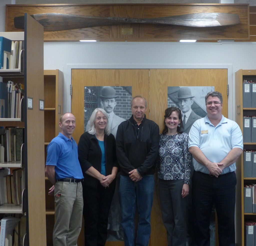 Staff take a photo with Conservator Stefan Dedecek under the 1905 Wright Taper Tip Propeller in the Reading Room. From Left to Right: Bill Stolz, Dawne Dewey, Stefan Dedecek, Toni Vanden Bos, Chris Wydman.