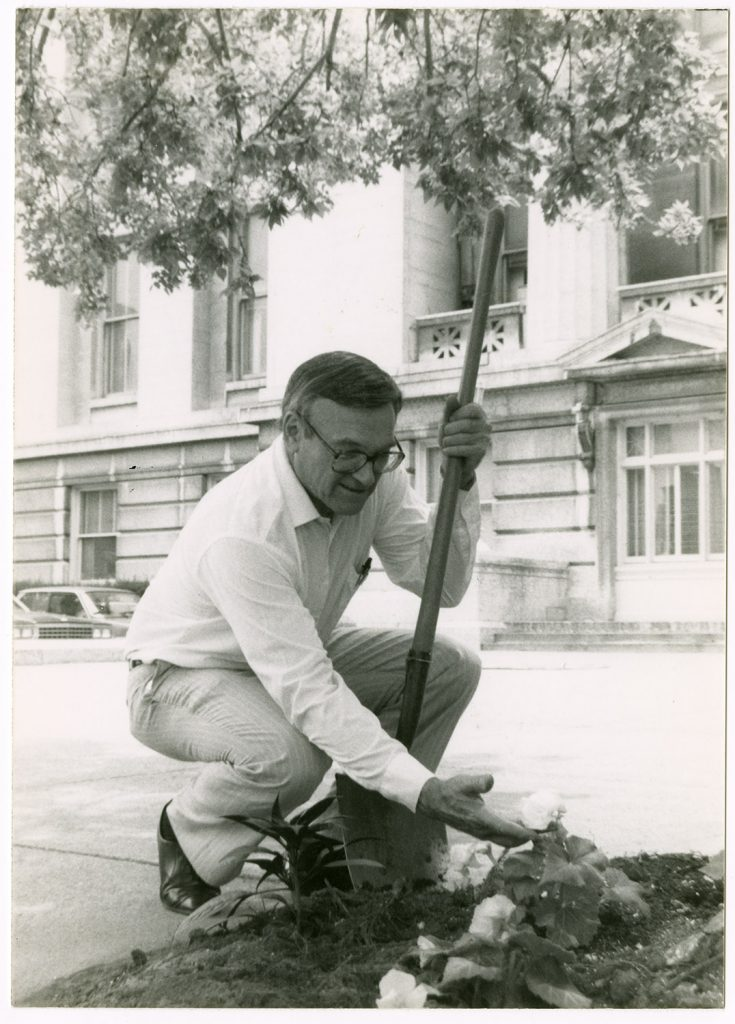 A photograph of senator Charles Horn planting marigolds outside of the Ohio State House. Horn was involved in beautification projects, particularly the planting of marigolds, throughout his political career. Circa 1984-2001. (ms629_018_001_001)